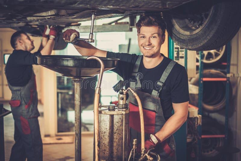 在汽车引擎的专业汽车修理师改变的机油在维护修理服务站在汽车车间 免版税库存图片