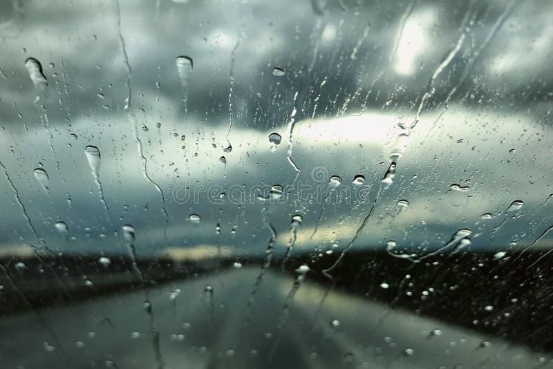 在汽车挡风玻璃的雨下落 雨天视图通过车窗 雨季概念 免版税库存图片