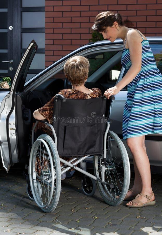 在汽车旁边的残疾和女儿 图库摄影