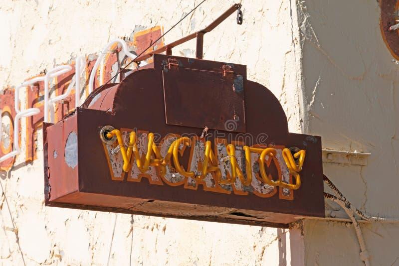 在汽车旅馆大厦的老生锈的空位标志 库存照片