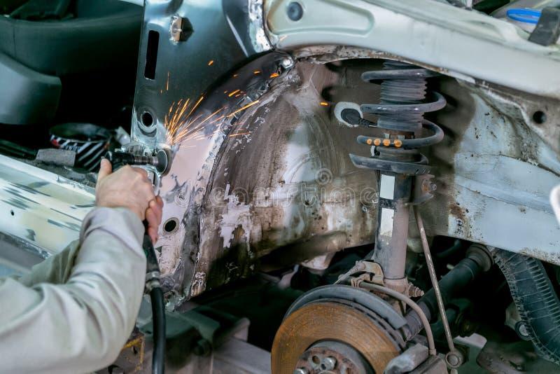 在汽车服务的汽车修理 技工工作者安装工铺沙的擦亮的车身和准备汽车绘的在期间 库存图片