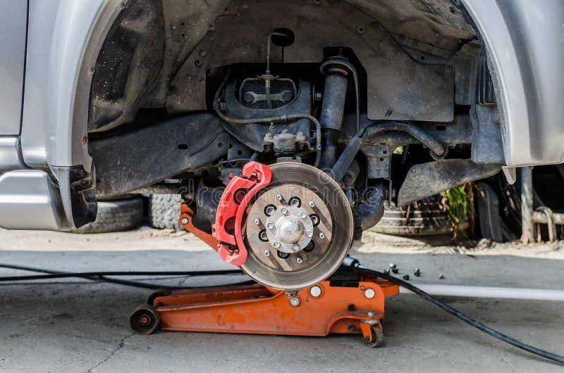 在汽车的前面盘式制动器在新的轮胎替换的过程中 免版税库存图片