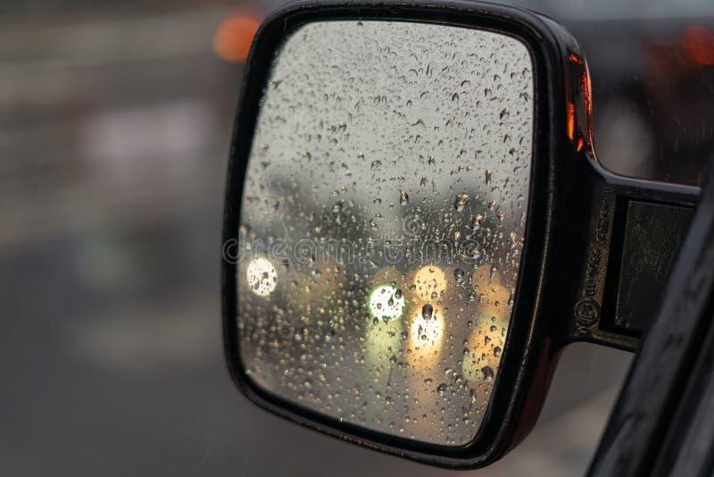 在汽车的后视镜的雨珠 反射,其他汽车车灯是在焦点外面 库存图片