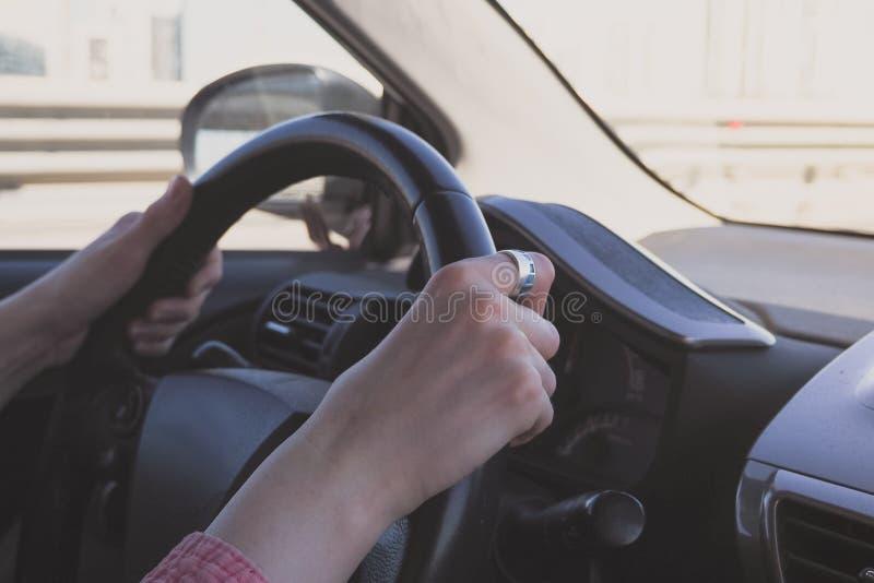 在汽车的方向盘的女性手,当驾驶时 免版税库存照片