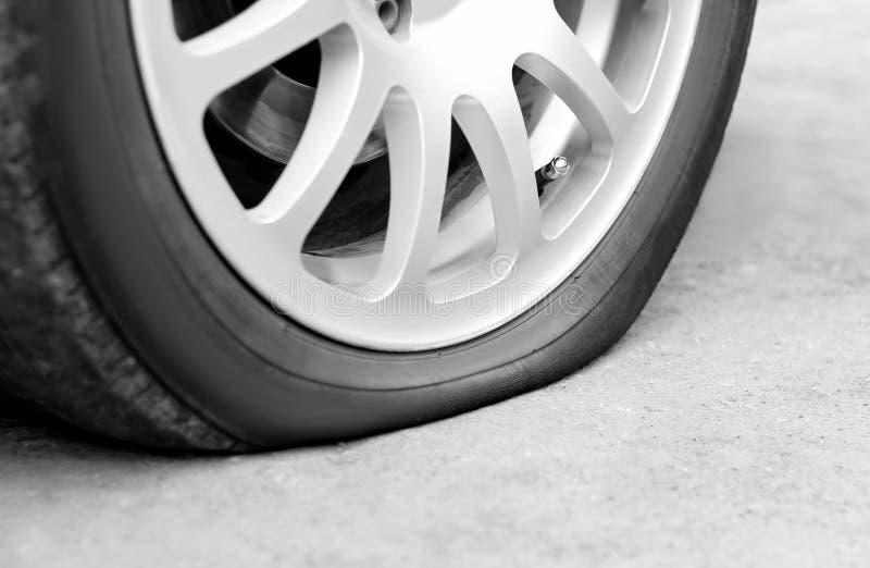 在汽车的泄了气的轮胎 银色伪造的轮子 ?? 库存照片