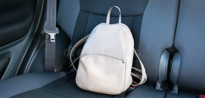 在汽车的灰色后座的米黄皮革背包 免版税库存图片