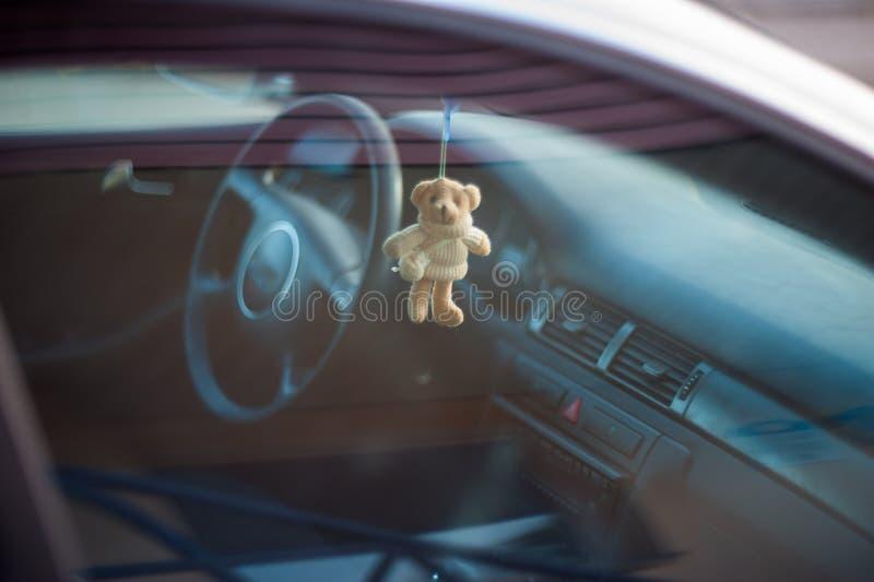 在汽车的玩具熊,垂悬在后视镜的软的玩具 免版税库存照片