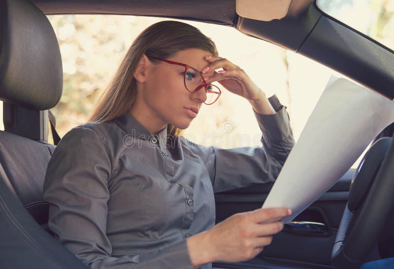 在汽车的生气妇女读书纸 图库摄影