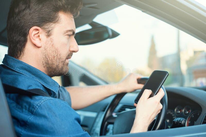 在汽车的男性使用在轮子的手机 库存图片