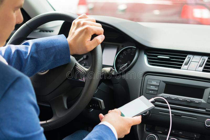 在汽车的轮子的司机打开从电话的音乐 免版税库存图片