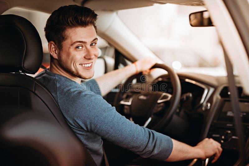 在汽车的轮子的后愉快的年轻司机 买汽车和驾驶概念 图库摄影
