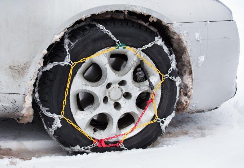 在汽车的防滑链在雪 免版税库存图片