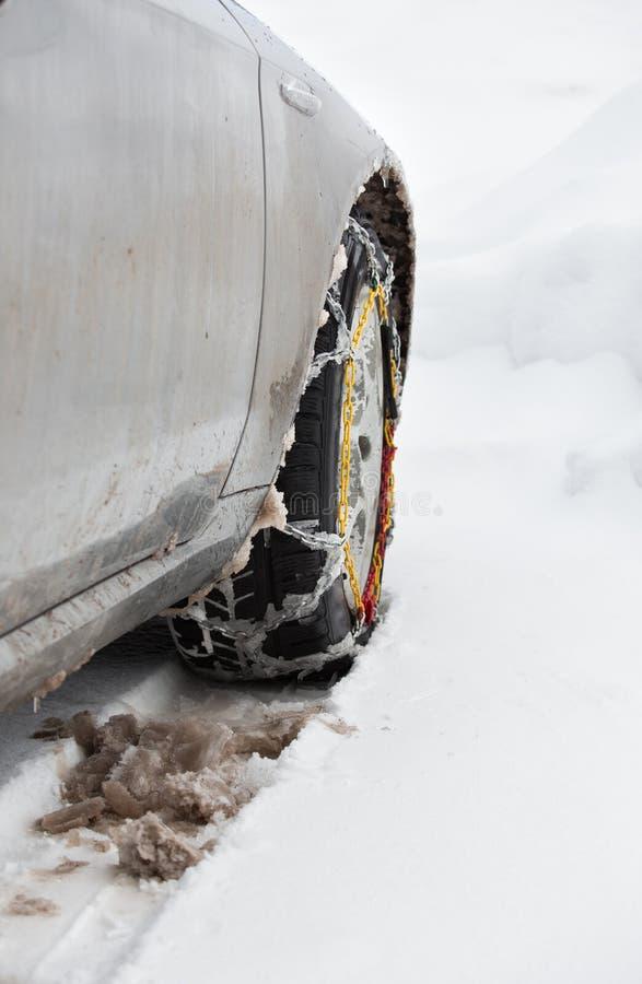 在汽车的防滑链在雪 库存图片