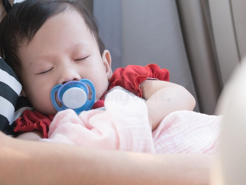 在汽车的婴孩睡眠有在嘴的安慰者的 免版税库存照片