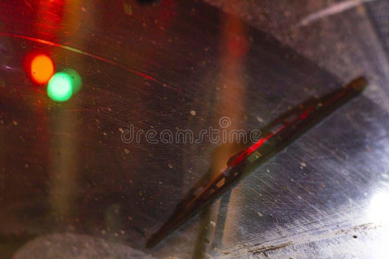 在汽车里面的刮水器在一块肮脏的被抓的挡风玻璃,雨季节,在晚上 前面和后面背景弄脏与 库存照片