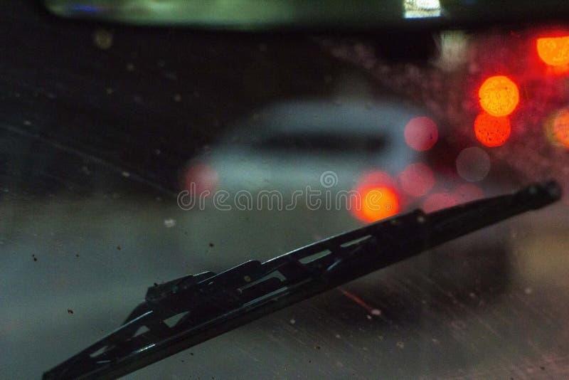 在汽车里面的刮水器在一块肮脏的被抓的挡风玻璃,雨季节,在晚上 前面和后面背景弄脏与 免版税库存照片