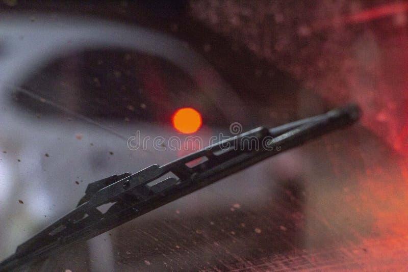 在汽车里面的刮水器在一块肮脏的被抓的挡风玻璃,雨季节,在晚上 前面和后面背景弄脏与 库存图片