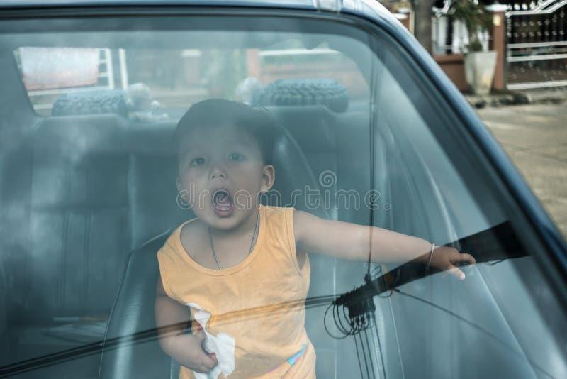 在汽车里面的快乐的男孩喜欢旅行在度假 库存照片