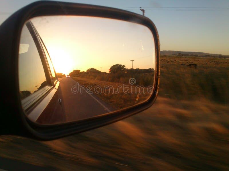 在汽车镜子的日落 免版税库存照片