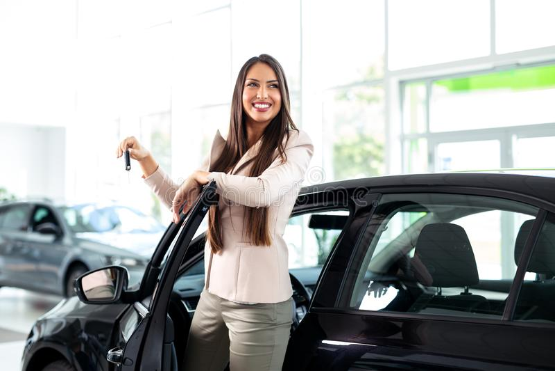在汽车附近的年轻愉快的妇女有钥匙在手中-买的新的汽车的 免版税库存照片