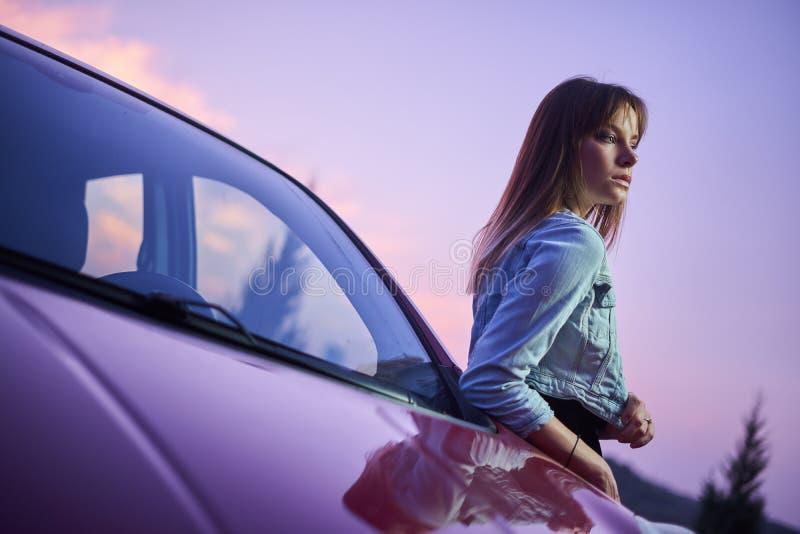 在汽车附近的美好的时兴女孩立场 库存图片