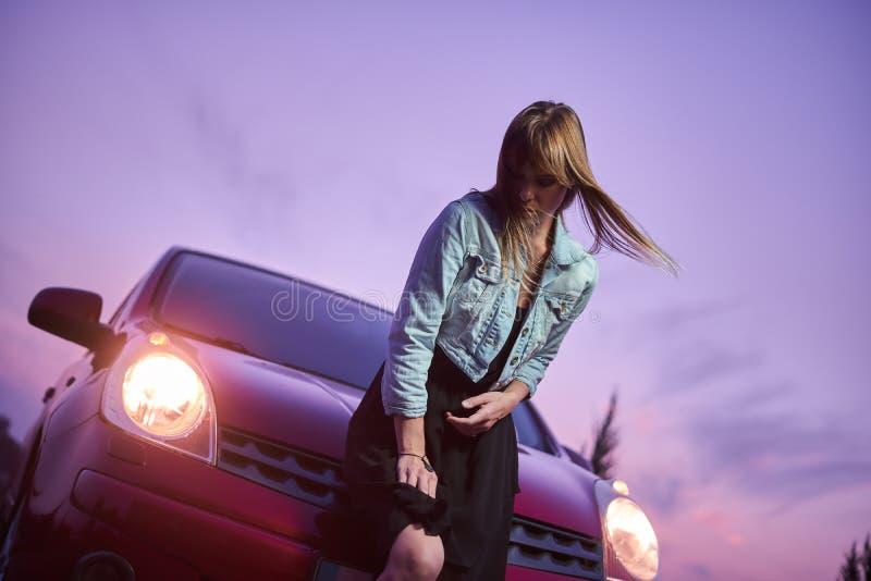 在汽车附近的美好的时兴女孩立场 免版税库存图片