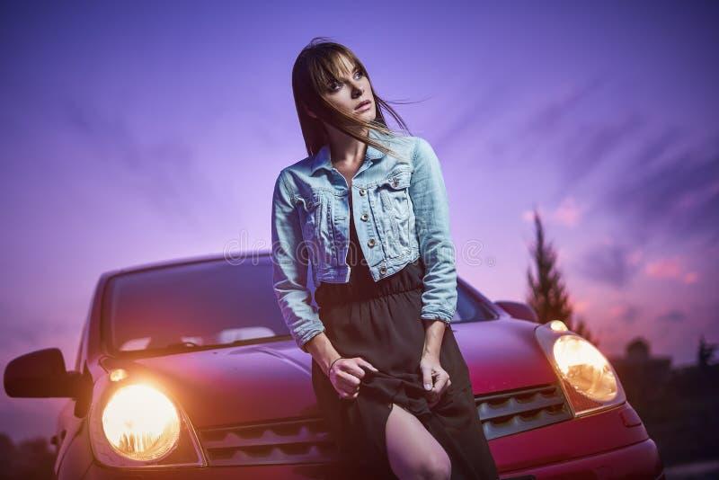 在汽车附近的美好的时兴女孩立场 免版税库存照片