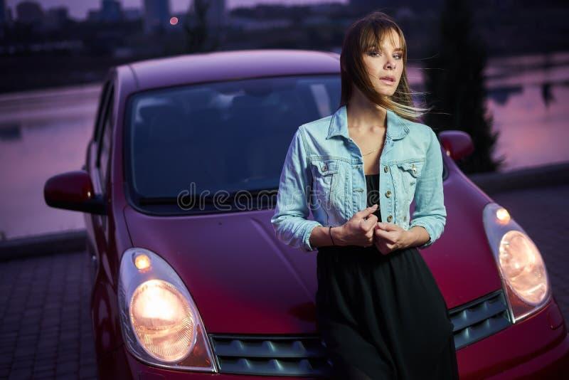 在汽车附近的美好的时兴女孩立场 免版税图库摄影