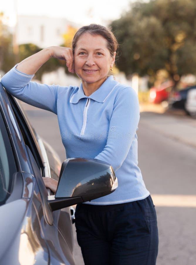在汽车附近的资深妇女 免版税库存图片