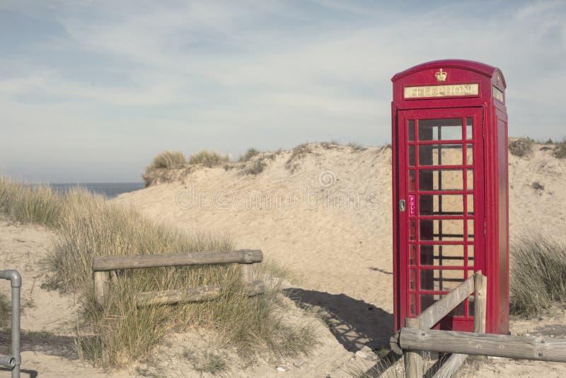 在沙丘的一个红色电话箱子在多西特 免版税库存照片