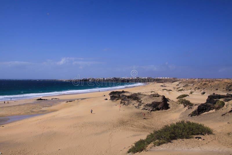 在沙丘的看法与Playa的在白色村庄的del Aljibe绿色海洋峭壁的El Cotillo -北部费埃特文图拉岛 图库摄影