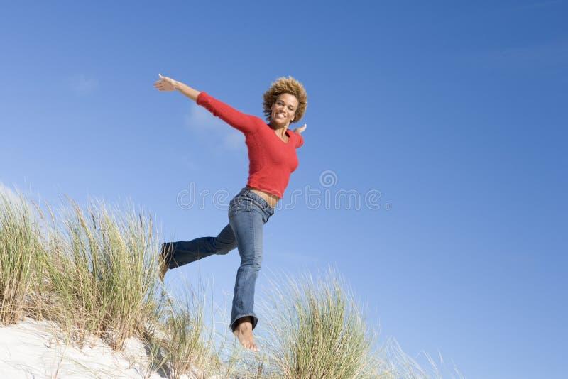 在沙丘跳之中铺沙妇女年轻人 免版税库存图片