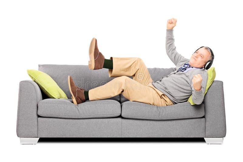 在沙发听的音乐安装的激动的资深男性 图库摄影