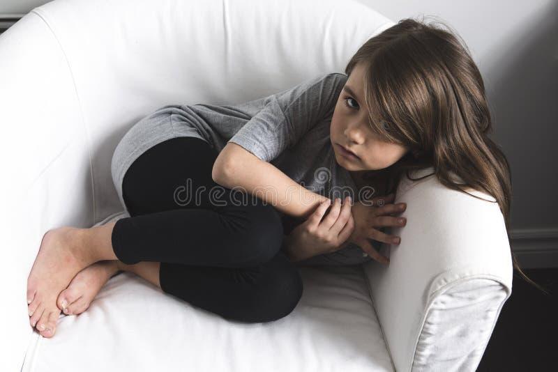 在沙发放置的哀伤的女孩 免版税库存图片