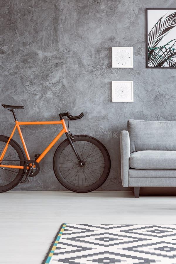 在沙发旁边的橙色自行车 库存照片