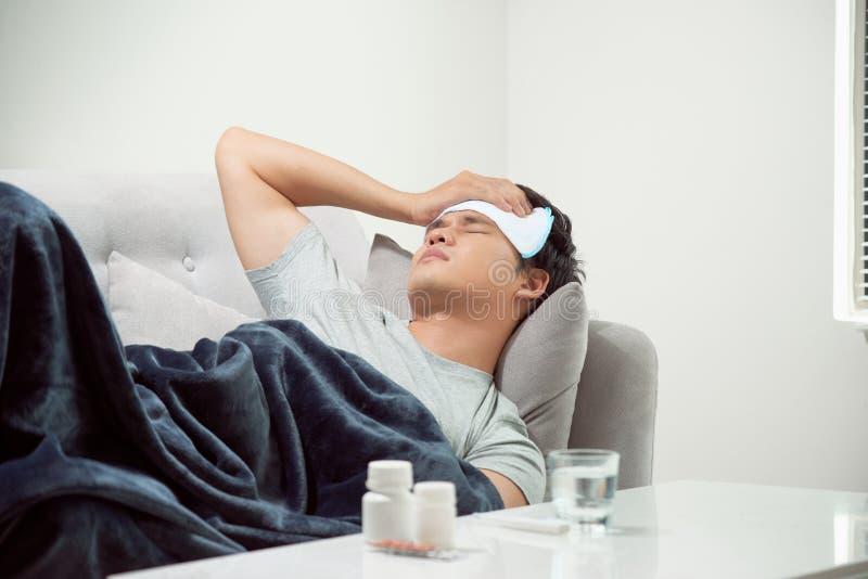 在沙发痛苦寒冷和冬天流感病毒的病的被浪费的人有医学片剂在医疗保健概念看 库存照片