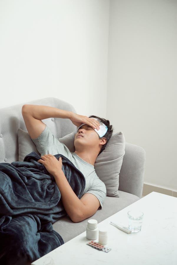 在沙发痛苦寒冷和冬天流感病毒的病的被浪费的人有医学片剂 免版税库存照片