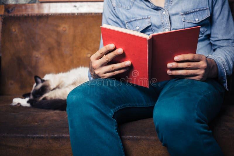 在沙发的人读书有猫的 免版税库存图片