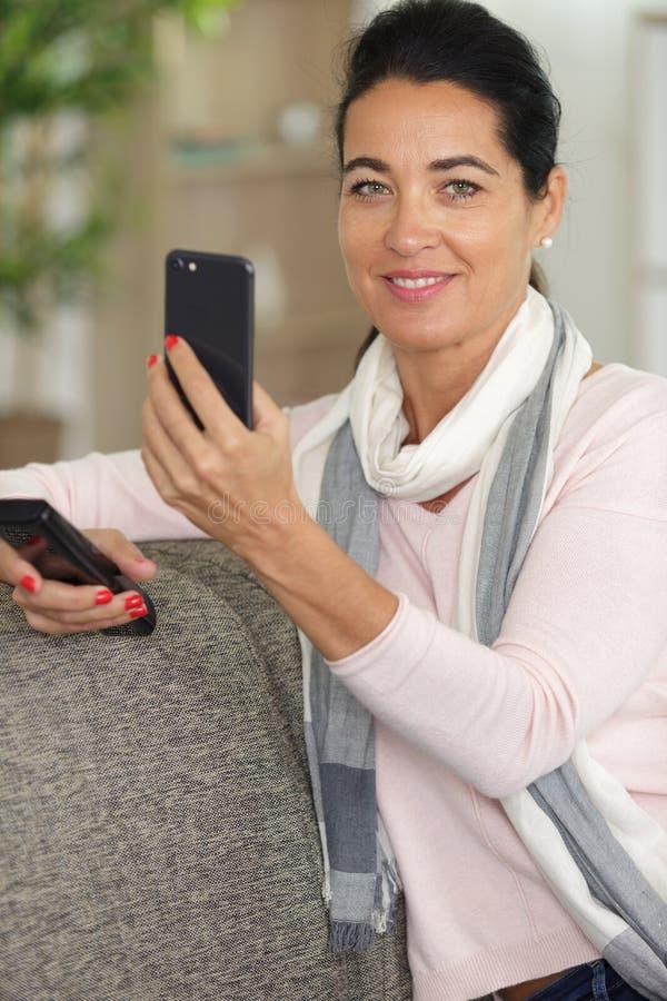 在沙发的俏丽的妇女selfie在客厅 免版税库存图片