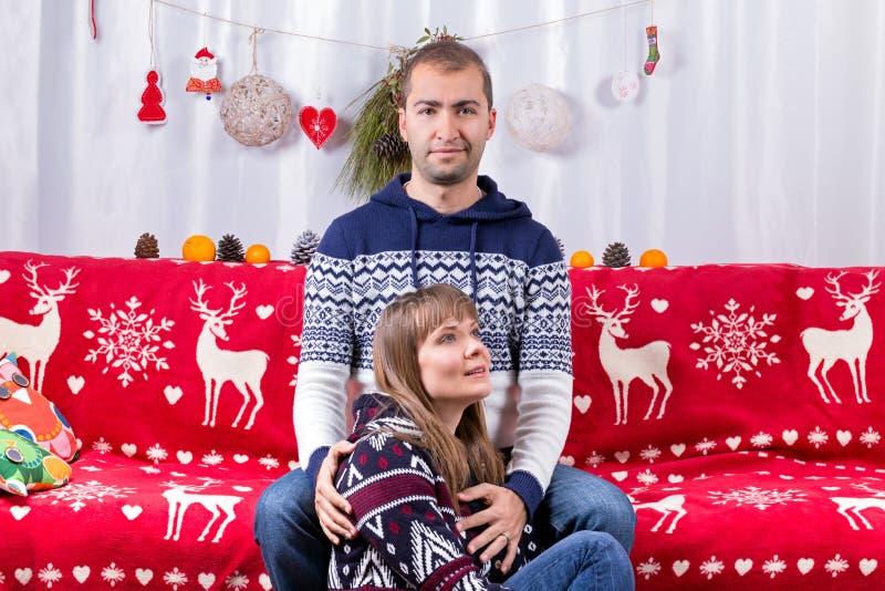 在沙发的圣诞节夫妇 库存图片