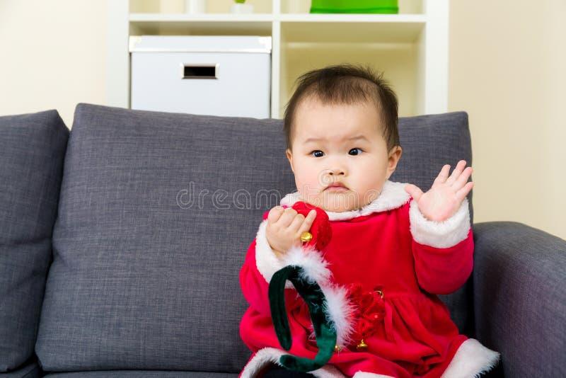 在沙发的女婴就座有圣诞节选矿的 图库摄影