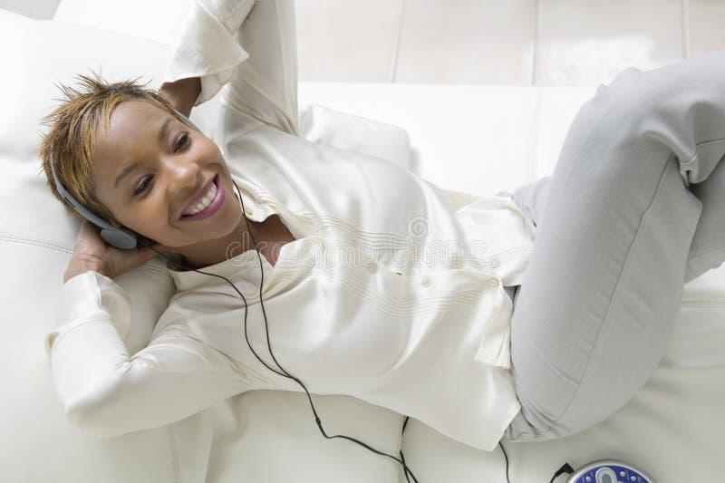 在沙发的妇女听的音乐 库存图片