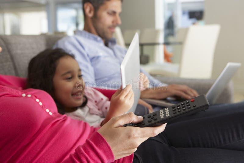 在沙发的家庭有膝上型计算机和数字式片剂的看电视的 免版税库存照片