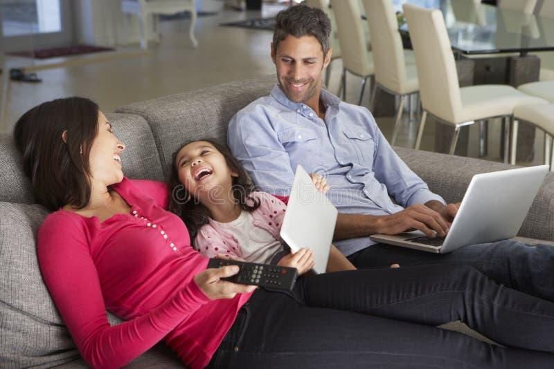在沙发的家庭有膝上型计算机和数字式片剂的看电视的 库存照片