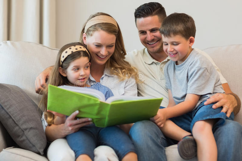在沙发的家庭观看的象册 库存图片