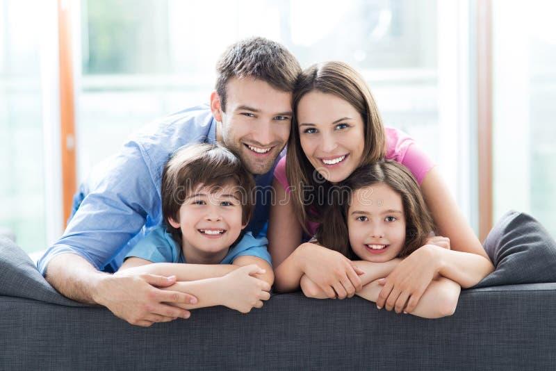 在沙发的微笑的家庭 图库摄影