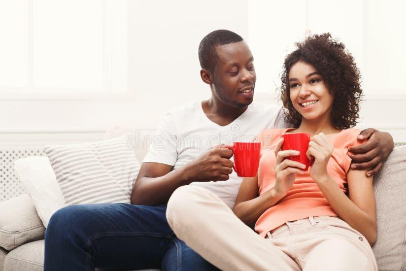在沙发的微笑的黑夫妇饮用的咖啡在家 免版税库存照片