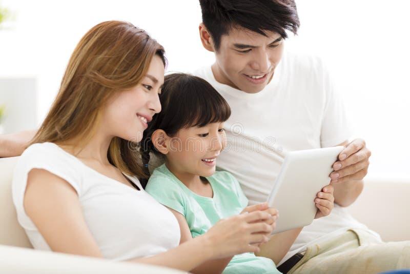 在沙发的愉快的家庭和女儿观看的片剂 库存图片