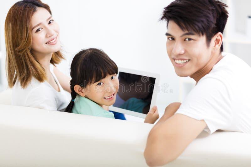 在沙发的愉快的家庭和女儿观看的片剂 免版税库存照片