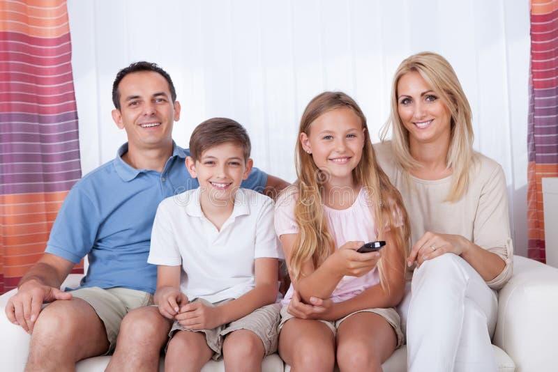 在沙发的愉快的家庭看电视的 图库摄影